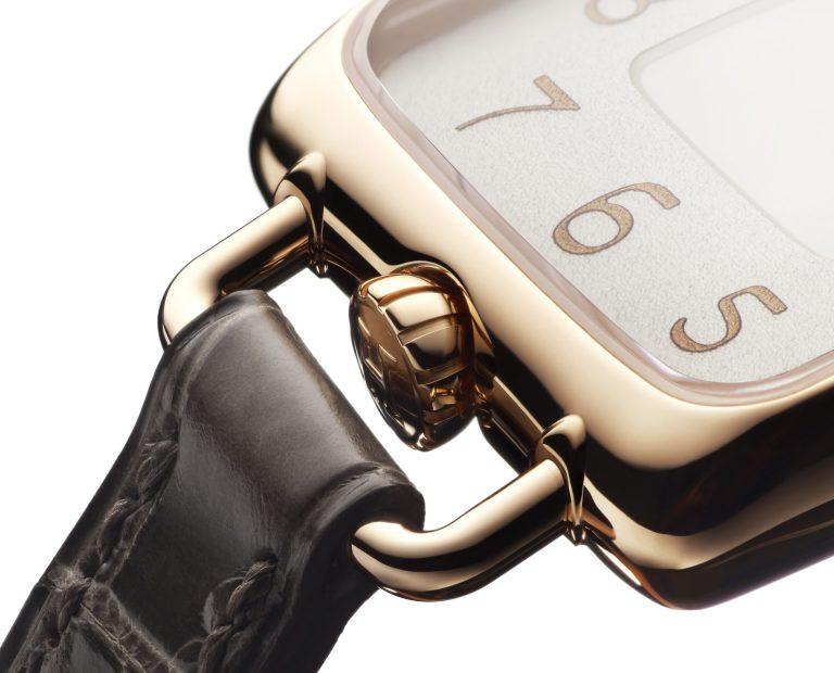 Die unten angebrachte Krone unterstützt die Hufeisenform der Uhr