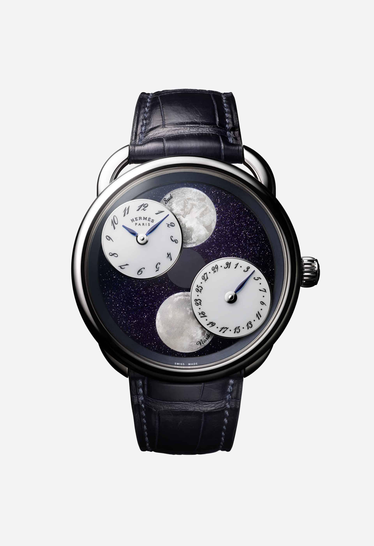 Die Mondscheiben und die rotierenden Uhrzeit-, bzw. Datumsscheibe vor nachtdunkler Oberfläche der hermes Armbanduhr